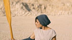 De militante en beslissende vrouw houdt een roeispaan in haar hand tegen de achtergrond van bergen Surrealistische scène stock video