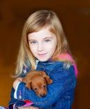 De mini mascotte van het pinnscherpuppy met blond jong geitjemeisje royalty-vrije stock foto