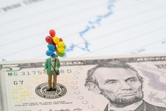 De miniatuur gelukkige mens die kleurrijke ballons op het embleem van de V.S. Federal Reserve op Amerikaanse dollarsbankbiljet ho stock foto's