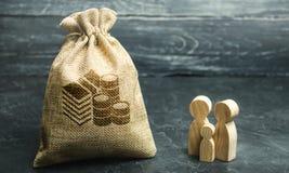 De miniatuur houten tribune van familiebeeldjes dichtbij een geldzak Het concept besparingen Begroting planning Distributie van w stock fotografie
