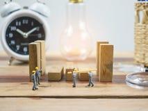 De miniatuurarbeider van de menseningenieur op houten lijst en witte achtergrond Stock Afbeeldingen