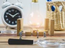 De miniatuurarbeider van de menseningenieur op houten lijst en witte achtergrond Stock Foto's