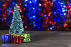 De miniatuurkerstboom met minikerstmisgiften op twee kleurt bokeh achtergrond Stock Foto