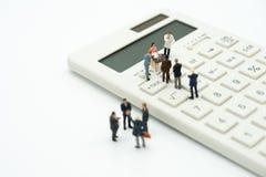 De miniatuurmensen betalen rij Jaarlijkse INKOMSTENBELASTING voor het jaar op calculator het gebruiken als achtergrond bedrijfsco stock fotografie