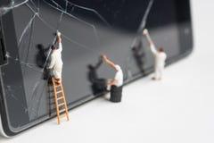 De miniatuurmensen proberen om het gebarsten slim telefoonscherm te herstellen royalty-vrije stock afbeeldingen