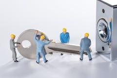 De miniatuurmensen proberen om metaalsleutel te openen stock foto