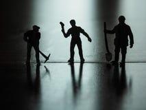 De miniatuurmensen silhouetteren, arbeider het graven op de vloer stock foto's