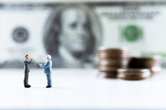 De miniatuurmensen, Zakenman status op dollarrekening met muntstukstapel voeren achtergrond op royalty-vrije stock fotografie