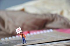 De miniatuurmensenholding van I houdt van u bericht in het document met mooie achtergrond Stock Afbeelding
