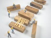 De miniatuurmenseningenieurs werken vol overgave en witte achtergrond Stock Afbeelding