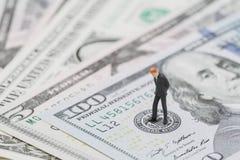 De miniatuurzakenmanleider status en het denken op het embleem van de V.S. Federal Reserve op vijf dollarsbankbiljet als EOF over royalty-vrije stock afbeelding