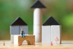De miniatuurzitting van de mensenbouwvakker op de houten Huisvesting van de Investeringsanalyse of investering in roerende goeder stock foto