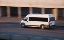 De minibus gaat op stadsweg Stock Afbeeldingen