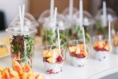 De minidesserts en de gezonde groente microgreen salades in plastic koppen canaps Richtende gediende lijst royalty-vrije stock afbeeldingen