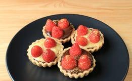 De minidiechocoladetaartjes en de roomtaartjes met verse aardbeien worden bedekt en het eetbare gouden poeder dienden op zwarte p stock fotografie