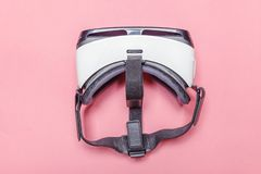 De minimale eenvoudige vlakte legt met virtuele de helmhoofdtelefoon van werkelijkheidsvr glazen op roze pastelkleur in moderne a stock afbeelding