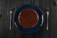 De minimalistische cake van de stijlchocolade op donkerblauwe plaat op zwarte tabl Royalty-vrije Stock Foto's