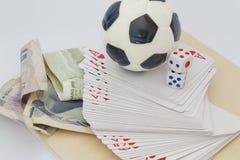 De minivoetbalbal bovenop spelenkaarten met dobbelt en geld in verschillende munt Concept het wedden en het gokken Royalty-vrije Stock Afbeelding