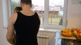 De minnaars die van hun nieuw huis genieten gaan de keukenholding handen en het kussen in stock video