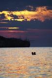 De minnaars doorweken in de zonsondergang Royalty-vrije Stock Foto's