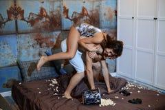 De minnaars leggen op het bed en zacht geknuffel in een uitstekende slaapkamer Stock Foto's