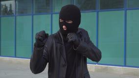 De misdadige de mensendief of rover in masker die zich in het in dozen doen bevinden stelt klaar voor slag stock video