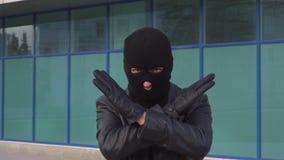 De misdadige de mensendief of rover in masker tonen het gebaar van het eindeteken door zijn handen te kruisen stock video
