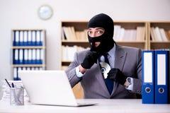 De misdadige zakenman die balaclava in bureau dragen stock foto's
