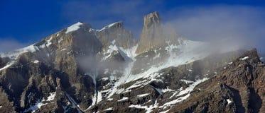 De mist in de bergen, ochtend, dageraad, hoge steenpieken is gewikkeld in lichte witte nevel, lichte lichtblauwe hemel, panoramis Stock Afbeeldingen