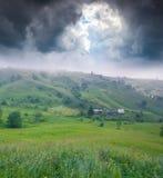 De mistige zomer mornnig in bergdorp stock afbeeldingen