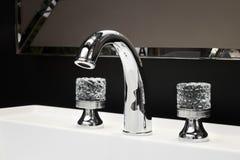 De mixer van de luxetapkraan met kristalhandvatten op een witte gootsteen in een mooie donkere badkamers Stock Foto's