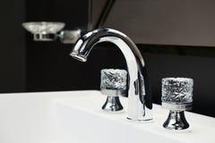 De mixer van de luxetapkraan met kristalhandvatten op een witte gootsteen in een mooie donkere badkamers Stock Afbeelding