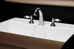 De mixer van de luxetapkraan met witte ceramische handvatten op een witte gootsteen in een mooie donkere badkamers Stock Foto's