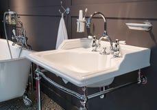 De mixer van de luxetapkraan met witte ceramische handvatten op een witte gootsteen in een mooie donkere badkamers Royalty-vrije Stock Afbeeldingen