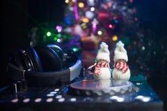 De mixer van DJ met hoofdtelefoons op donkere nachtclubachtergrond met de Vooravond van het Kerstboomnieuwjaar Sluit omhoog menin stock afbeeldingen