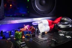 De mixer van DJ met hoofdtelefoons op donkere nachtclubachtergrond met de Vooravond van het Kerstboomnieuwjaar Sluit omhoog menin royalty-vrije stock afbeeldingen
