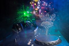 De mixer van DJ met hoofdtelefoons op donkere nachtclubachtergrond met de Vooravond van het Kerstboomnieuwjaar Sluit omhoog menin royalty-vrije stock foto's