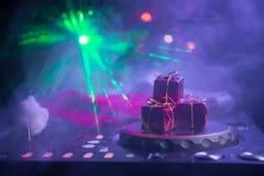 De mixer van DJ met hoofdtelefoons op donkere nachtclubachtergrond met de Vooravond van het Kerstboomnieuwjaar Sluit omhoog menin stock foto