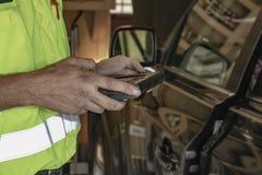 De mobiele automobieltechnicus controleert een auto met zijn computerapparaat met de cliëntengarage nadenkend in de auto hij werk stock afbeeldingen