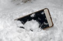 De mobiele die telefoon viel toevallig uit en werd in de sneeuw wordt verloren stock fotografie
