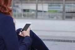 De mobiele slimme telefoon wordt gehouden op handen van bedrijfsvrouw op de gang tegen exemplaarruimte op de stadsachtergrond stock fotografie