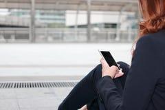 De mobiele slimme telefoon wordt gehouden op handen van bedrijfsvrouw tegen exemplaar ruimteachtergrond Het concept van het stads royalty-vrije stock foto