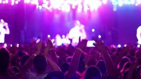De mobiele telefoon doet videorotsoverleg, de Gadget gefilmde scène met heldere gekleurde lichten, zijn vele mensen ventilators, stock footage