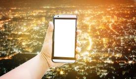 De mobiele telefoon van de mensengreep op de achtergrond van de handstad Royalty-vrije Stock Fotografie