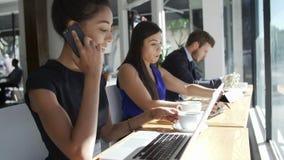 De Mobiele Telefoon van onderneemsterusing laptop and in Koffiewinkel stock footage
