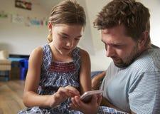 De Mobiele Telefoon van vaderand daughter using in Speelkamer samen stock afbeeldingen