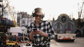 De moda, morenita en las gafas de sol que caminan en la calle y escuche la música en auriculares danzas Sosteniendo el móvil aden almacen de metraje de vídeo