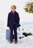 De moda, siete años del muchacho en la capa, sosteniendo el bolso al aire libre Fotos de archivo libres de regalías