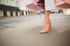 De moda vistió a la mujer en las calles de una pequeña ciudad, concepto que hacía compras imagenes de archivo