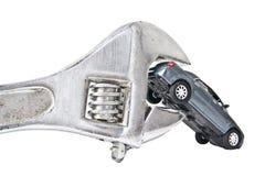 De modelauto van het stuk speelgoed die in moersleutel wordt vastgeklemd Stock Fotografie
